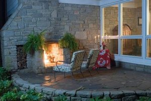 Installing a stone patio reduces maintenance and provides a cozy outdoor living area.