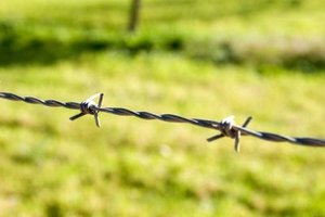 Install a barbed wire fence with special tools.