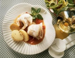 Stuffed sole fillet presented in tomato sauce.