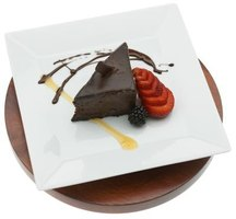 Use chocolate sauce to garnish a plate with a piece of chocolate cake.