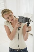 An electric drill is used to drill a hole into drywall.
