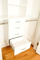This closet organization system includes drawers and double hanging space.