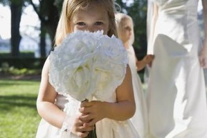 It is tradition for the flower girl to toss petals down the aisle, but what she drops or carries is up to you.