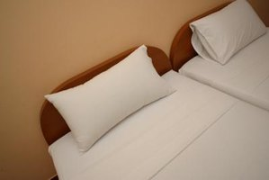 Check hotel bedding for signs of bed bug infestation.
