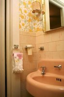 Typical 1950s bathrooms featured colored appliances and tile, wallpaper, built-in accessory holders and sconces.
