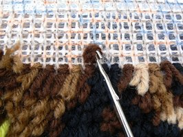 In latch hooking you use a small hooked tool to pull yarn through the holes in a canvas.