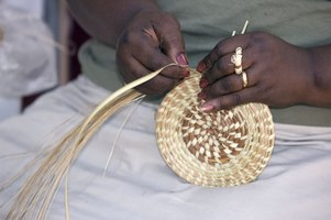 African woman weaving a basket with pine needles