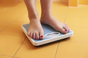 A close-up of a woman standing on a bathroom scale.