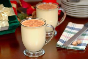 Two glasses of eggnog garnished with nutmeg.