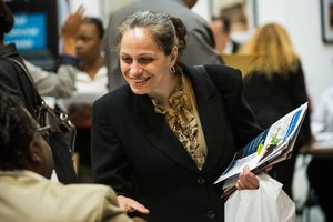 A candidate carrying a flyer while networking at a job fair.