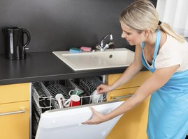 Woman using dishwasher.
