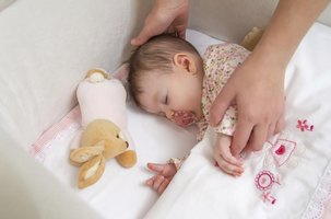 A baby with a pacifier sleeping in a crib.