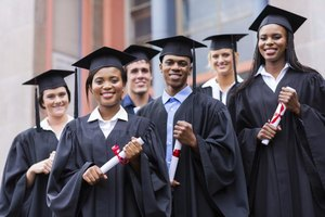 Group of young economy graduates holding degrees