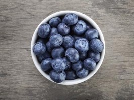 A bowl of fresh blueberries on a rustic table.