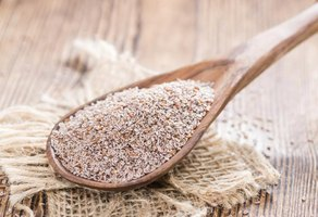 A wooden spoon filled with psyllium husks.