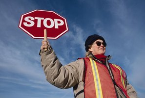 School crossing guard holding up stop sign.