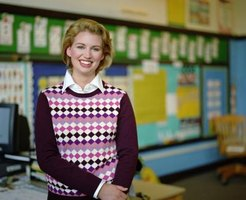 A young teacher is smiling in her classroom.