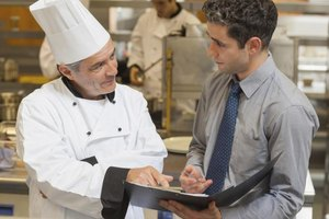 A food service specialist and chef reviewing a checklist.