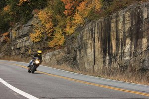 Motorcycle driving on road during autumn.