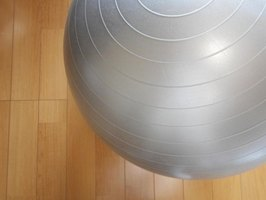 An overhead view of a fitness ball on a wood floor.