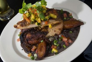 Traditional jerk chicken on a plate served with black beans and rice, plantains, cilantro and fresh mango salsa.