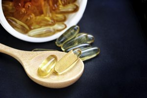 Small wooden spoon with fish oil supplements on it.