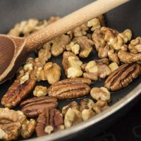 Pecans are darker and have a distinctive oval shape.