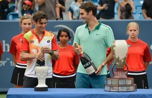 Tennis champion Roger Federer holds a bottle of champagne next to his opponent and trophy.