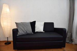 Most black couches are in spare, often curtainless rooms.