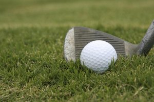 A pitching wedge lined up behind a golf ball on grass.