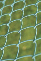 Keep your yard private with homemade slats for a chain link fence.
