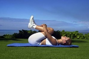 The roll-over stretch begins in a supine position with your knees close to your chest.