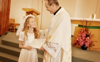 Girl receiving a certificate for taking her First Communion.