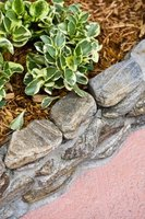 Stones enhance the look of raised flower beds.