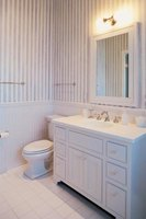 A bathroom's wainscoting covers the wall next to the sink's cabinet.