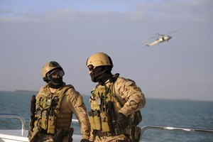 Navy SEALs speaking together on ship.