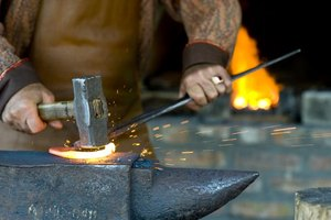 A blacksmith hammers a piece of steel.