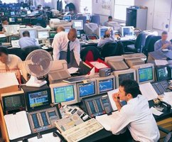 Stock brokers in front of numerous computer screens.