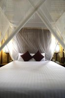 A sheer white bed canopy mimics the mosquito netting used on beds in real rain forest settings.