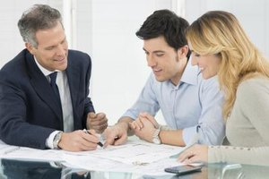 A couple signing documents, sitting next to a mortgage lender
