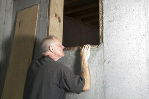 A man looks into a crawl space that is under a house.