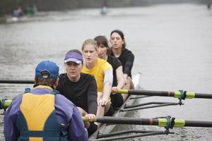 A coxswain in a boat practicing with a female rowing crew.