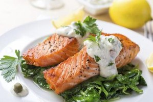 Plate of grilled salmon with sauce drizzled on top of it.