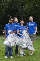 Kids use clear garbage bags to clean the park.