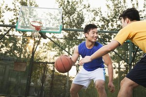 Two young men playing basketball on an outdoor court.