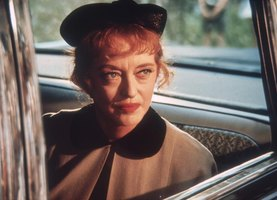American film star, Bette Davis, looking out a car window on the big screen.