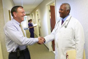 A healthcare administrator shakes hands with a medical professional.
