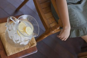A woman relaxing on the porch with a pitcher of lemon water.
