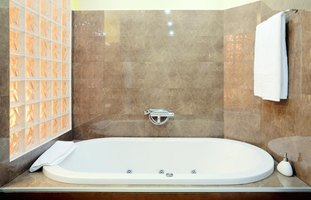 A contemporary sunken tub in a tile and glass block alcove.