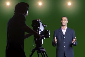 Man being filmed in front of a green screen.